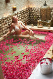 Woman Relaxing In Flower Petal Covered Pool. At Spa Stock Photos