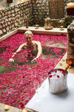 Woman Relaxing In Flower Petal Covered Pool At Spa Royalty Free Stock Photos