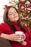Woman relaxing in front of Christmas tree Royalty Free Stock Images