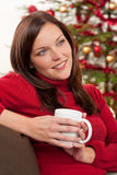 Woman relaxing in front of Christmas tree Royalty Free Stock Photo