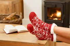 Woman relaxing in front of fire. Woman in Christmas socks relaxing next to a wood burning stove Stock Photos