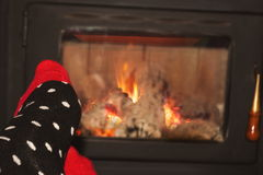 Woman relaxing in front of fireplace Stock Photography
