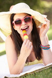 Woman Relaxing In Garden Eating Ice Lolly. Wearing Sun Hat and Sunglasses Royalty Free Stock Photos