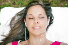 Woman relaxing on the grass while listening music Stock Photo