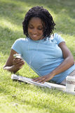 Woman relaxing on grass in park, listening to MP3 player, reading newspaper, smiling (tilt) Royalty Free Stock Image