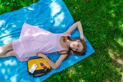 Pretty young woman relaxing on the grass in a park listening to music on her mobile phone stock photo