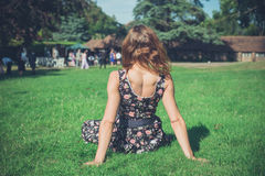 Woman relaxing on grass at party Stock Images