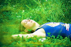 Woman relaxing in green field stock images