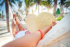 Woman relaxing in the hammock. Between palm trees Stock Photos