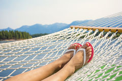 Woman relaxing in a hammock on a beautiful Mountain Lake Stock Image