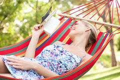 Woman Relaxing In Hammock With Book Royalty Free Stock Photography