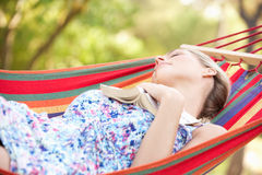 Woman Relaxing In Hammock With Book stock images