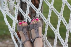Woman relaxing in the hammock at the garden with beautiful pedicure stock photos