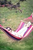 Outdoors relaxing leisure. Woman relaxing in hammock outdoors in a green park Royalty Free Stock Photo
