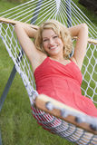 Woman relaxing in hammock smiling Stock Image
