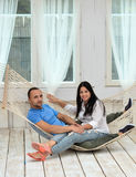 Woman relaxing in hammock smiling and man sitting Royalty Free Stock Photos