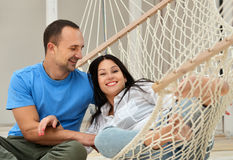 Woman relaxing in hammock smiling and man sitting Royalty Free Stock Image