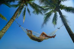 Woman relaxing on a hammock at the tropical beach resort. Woman relaxing on a hammock at the tropical beach royalty free stock image