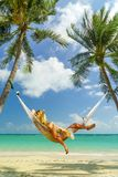 Woman relaxing on a hammock at the tropical beach resort. Woman relaxing on a hammock at the tropical beach royalty free stock photography