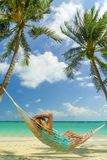 Woman relaxing on a hammock at the tropical beach resort. Woman relaxing on a hammock at the tropical beach stock image
