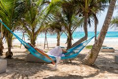 Woman relaxing in a hammock on a tropical beach. With palm trees and turquoise waters Royalty Free Stock Images