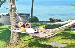 Woman relaxing in the hammock on tropical beach. At Samui islands, Thailand Stock Photos