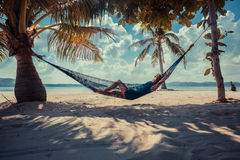 Woman relaxing in hammock on tropical beach. A young woman is relaxing in a hammock on a tropical beach Stock Photography