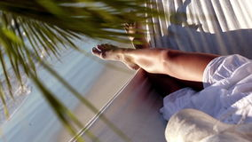 Woman relaxing in a hammock under a palm tree. On a sunny beach stock footage