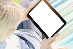 Woman relaxing in a hammock using a digital tablet. Over the shoulder view of a woman relaxing in a hammock using a digital tablet Royalty Free Stock Photos
