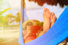 Woman relaxing in hammockwith touch pad at the sea Royalty Free Stock Photos