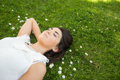 Woman relaxing with hand behind head on grassland Royalty Free Stock Photo