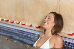 Woman relaxing happy in a spa jacuzzi. Woman bathing and relaxing happy in a spa jacuzzi with candles and rose petals Royalty Free Stock Image