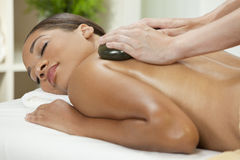 Woman Relaxing Having Hot Stone Treatment Massage. An African American woman relaxing at a health spa while having a hot stone treatment or massage stock photography