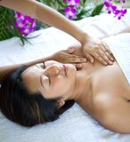 Woman relaxing while having spa treatment. Young woman relaxing while having spa treatment with warm pebbles Stock Photos