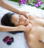 Woman relaxing while having spa treatment. Young woman relaxing while having spa treatment with warm pebbles Royalty Free Stock Photos
