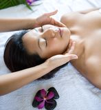Woman relaxing while having spa treatment. Young woman relaxing while having spa treatment with warm pebbles Stock Photography