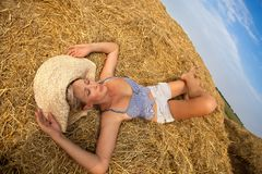 Woman relaxing in hay stack Stock Images
