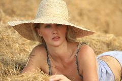 Woman relaxing in hay stack Stock Photo