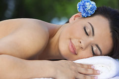 Woman Relaxing At Health Spa With Blue Flower. A beautiful brunette hispanic latina woman relaxing outside on a massage table at a health spa with a blue flower Stock Image