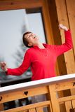 Woman relaxing on her balcony in winter. Happy woman relaxing on her balcony arms in the air in winter stock photography