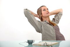 Woman relaxing at her desk royalty free stock photography