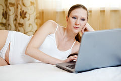 Woman relaxing with her laptop  on a bed at home Stock Photography