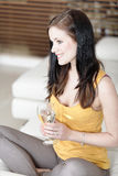 Woman relaxing on her sofa with a drink royalty free stock image