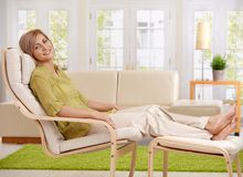 Woman relaxing at home. Sitting in armchair with crossed feet up on footboard, smiling at camera Royalty Free Stock Photography