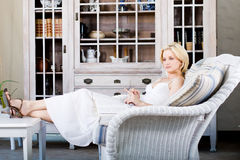 Woman relaxing at home. Beautiful blond woman relaxing at home on the sofa Royalty Free Stock Photos