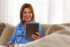 Woman relaxing at home with breakfast and digital tablet stock photography