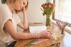 Woman relaxing at home by coloring book. Woman drawing an adult coloring book while comfortably sitting at table by a window Royalty Free Stock Images
