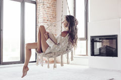 Woman relaxing at home in hanging chair Stock Images