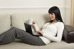 Woman  relaxing at home with her computer Royalty Free Stock Image