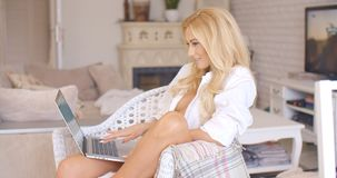 Woman relaxing at home with her laptop computer Stock Photography